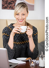 Smiling beautiful blond woman drinking a coffee