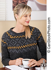 Smiling beautiful blond woman in a coffee shop
