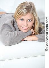 Smiling beautiful blond woman laying on sofa