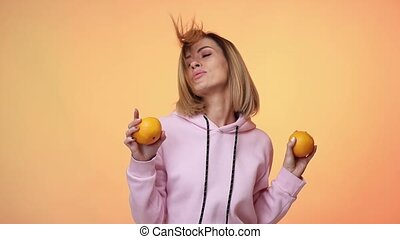 smiling beautiful blonde caucasian woman in casual pink clothes holding oranges and dancing on pink color background in studio. slow motion