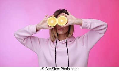 smiling beautiful blonde caucasian woman in casual pink clothes holding oranges and dancing on pink color background in studio.