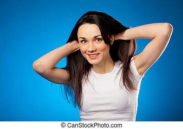 smiling beautiful brunette girl in white t-shirt over blue background in studio