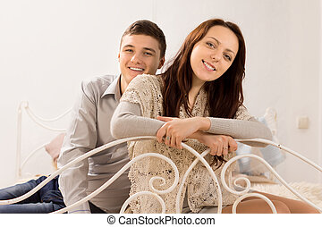 Smiling beautiful couple on a wrought iron bed