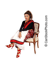 Smiling beautiful East Indian woman sitting in armchair