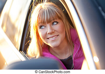 Smiling beautiful girl looks out of a car window