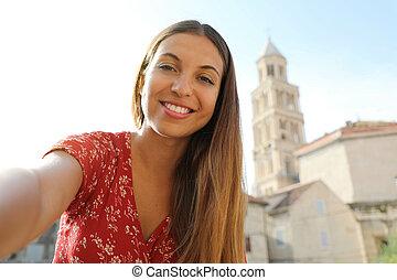 Smiling beautiful girl take self portrait in Split, Croatia, Europe