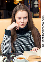 Smiling beautiful girl with book posing in cafe