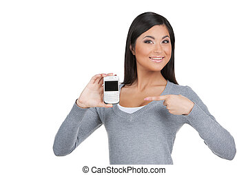 Smiling beautiful Indian girl showing with finger on phone. Standing isolated over white background