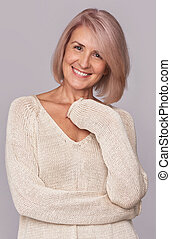 smiling beautiful mid aged woman isolated on grey background