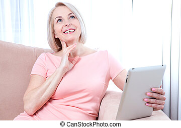 Smiling beautiful middle-aged woman sitting on couch with a tablet, considering new idea.