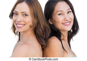 Smiling beautiful nude models posing back to back