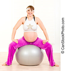Smiling beautiful pregnant female doing pilates exercises on gray ball