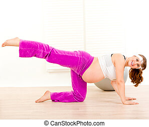 Smiling beautiful pregnant woman doing aerobics exercise...