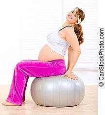 Smiling beautiful pregnant woman doing pilates exercises on...