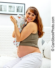 Smiling beautiful pregnant woman sitting on sofa at home with baby clothes in hands.