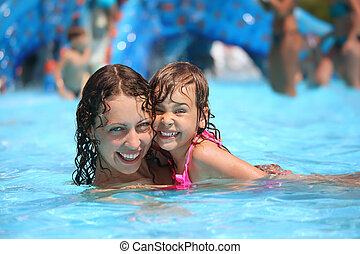 Smiling beautiful woman and little girl bathes in pool in ...