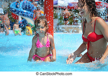 Smiling beautiful woman and little girl bathes in pool under water splashes