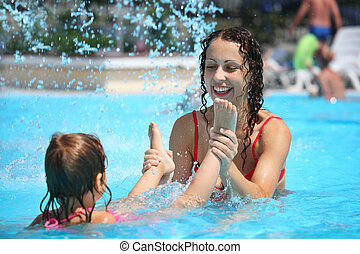 Smiling beautiful woman and little girl bathes in pool under water splashes, woman holds girl for feet