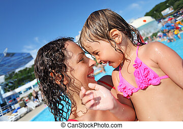 Smiling beautiful woman and little girl bathing in pool of an entertaining complex, concerning with heads
