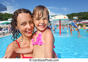 Smiling beautiful woman and little girl bathing in pool of an entertaining complex