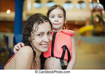 Smiling beautiful woman and little girl  in lifejacket after swimming in covered pool