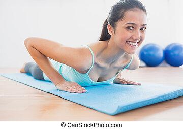 Smiling beautiful woman doing push ups in gym