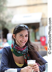 Smiling beautiful woman drinking cappuccino