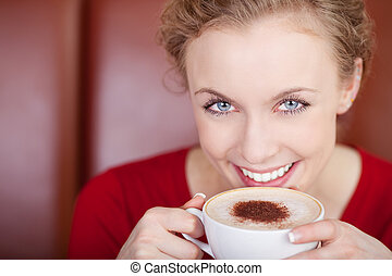smiling, beautiful woman drinking cappuccino