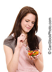 smiling beautiful woman eating mixed salad on white background