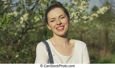 Smiling beautiful woman near blossoming tree