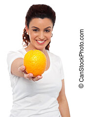 Smiling beautiful woman offering you an orange