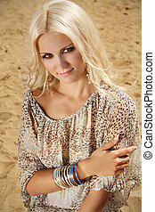 Smiling beautiful woman relaxing on sand beach