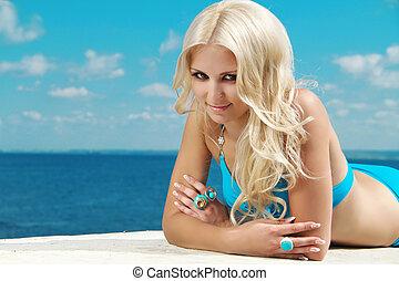 Smiling beautiful woman sunbathing on beach sea