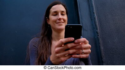 Smiling beautiful woman texting on mobile phone 4k - Smiling...