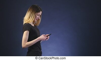 smiling beautiful woman texting with her phone black background side view
