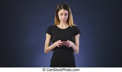 smiling beautiful woman texting with her phone black background