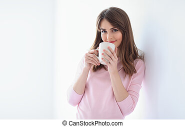 Smiling beautiful woman with cup of coffee on white background