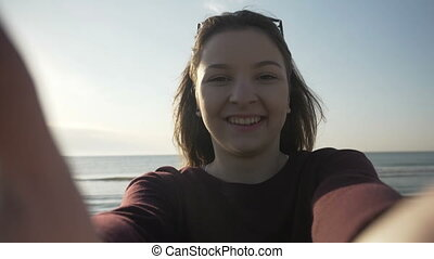 Smiling beautiful woman with sunglasses taking selfie using...