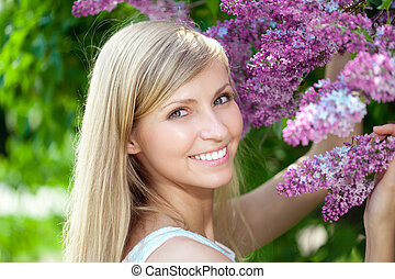 Portret of smiling beautiful woman with violet flowers