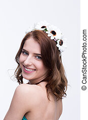 Smiling beautiful woman with wreath over gray background