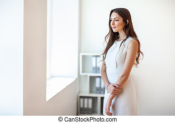 Smiling beautiful young business woman in office