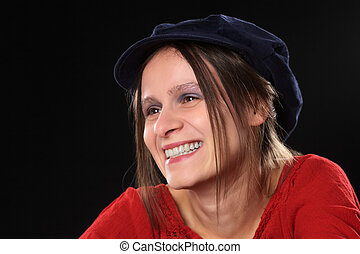 Smiling beautiful young Caucasian woman with a blue gatsby cap (Selective Focus, Focus on the left eye)