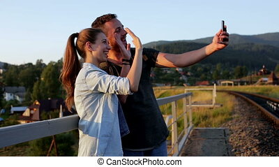 Smiling beautiful young couple taking pictures with smartphone in mountains