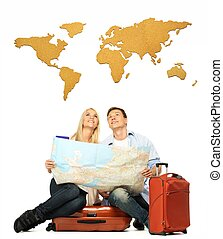 Smiling beautiful young couple with a map sitting on a suitcase