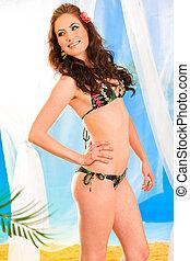 Smiling beautiful young girl in bikini with flower in hair posing in summerhouse on beach.