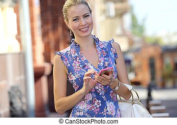 smiling beautiful young girl with phone in hand