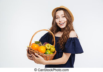 Smiling beautiful young woman in hat holding basket with fruits