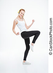 Smiling beautiful young woman in headphones dancing