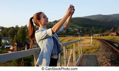 Smiling beautiful young woman taking pictures with smartphone in mountains