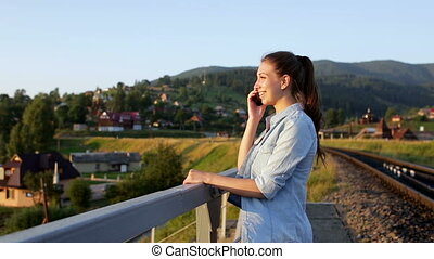 Smiling beautiful young woman with smartphone in mountains